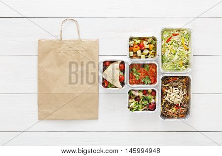 Healthy food delivery. Take away of natural organic low carb diet. Fitness nutrition in foil boxes, cutlery and brown paper package bag. Top view, flat lay with copy space at white wood