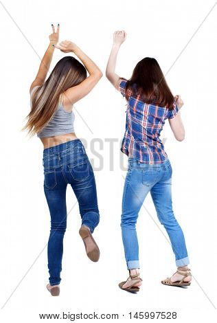 Back view of two dancing young women. Dance party. girls teens dance, enjoy and express positive emotions and having fun. Two young girls in jeans dancing