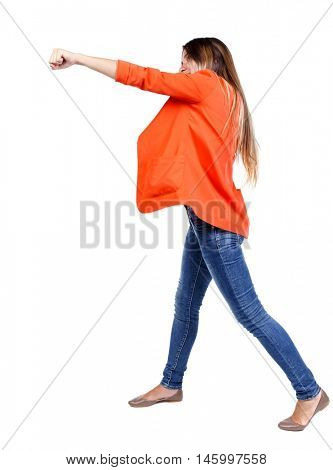back view of woman funny fights waving his arms and legs. Rear view people collection. girl in a red jacket stands sideways and strike his hand.