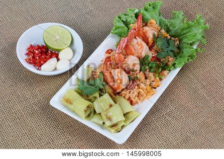 Fried rice with shrimp and grilled green sweet chili with side dish as sliced red hot chili pepper ,halved green lemon and garlic on brown. side view