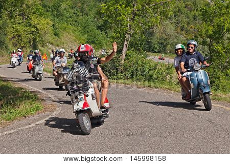 CESENA, ITALY - JUNE 26: group of bikers riding a vintage italian scooters Vespa on the hills during the scooter rally