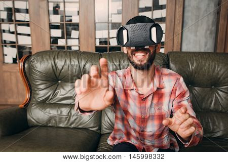 Man touching invisible keyboard in vr glasses. Young male in virtual reality headset touching objects in interactive environment, free space
