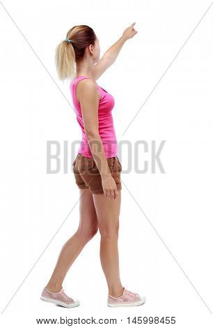 back view of pointing walking woman. going girl pointing. Sport blond in brown shorts is by pointing to the sky.
