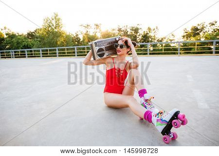 Young pretty brunette roller girl in sunglasses and red swimsuit listening music with old record player while sitting on the open road