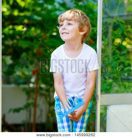 Caucasian little kid boy watering plants and vegetables with can and working with garden hoe in greenhouse. Preschool child helping on sunny summer day. Family, garden, gardening, lifestyle