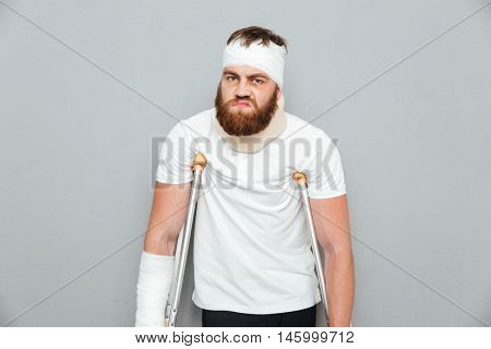 Unhappy irritated young man standing with crutches over white background