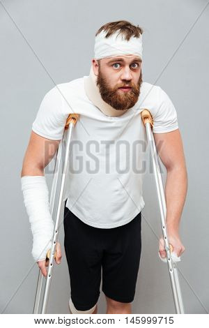 Amazed confused young man with injures standing using crutches over white background