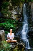 Beautiful young woman meditating and showing a lotus flower while doing yoga in the nature near wate