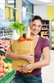 picture of healthy food  - Young woman holding a grocery bag full of fresh and healthy food in a supermarket - JPG