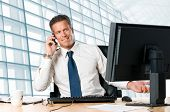 Successful businessman sit at his desk while talking on mobile in office