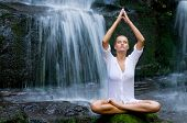 Beautiful young woman meditating in lotus position while doing yoga between waterfalls