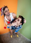 stock photo of sock-monkey  - Two handsome men playing piggyback in front of green and orange walls - JPG