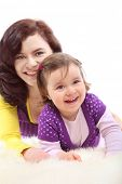Happy mother in colored clothes embraces her laughing little daughter on white fluffy fur, daughter in focus poster
