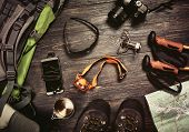 Hiking accessories set on dark wooden background:  boots, backpack, sunglasses, photo camera, map, s poster
