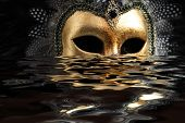 picture of masquerade mask  - Venetian mask decorated with gold leaf and embedded with fowl feathers with reflection on water - JPG