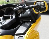 stock photo of console-mirror  - Side mirror and control console of a bright yellow motorcycle - JPG