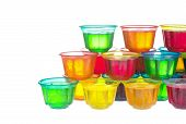 picture of unnatural  - Colorful jellies in plastic bowls arranged like a pyramid on white - JPG