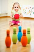 stock photo of little young child children girl toddler  - Adorable toddler girl playing bowling at home - JPG