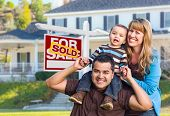 Happy Mixed Race Young Family in Front of Sold Home For Sale Real Estate Sign and House. poster