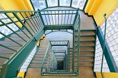 image of bannister  - Looking down a 7 story staircase with green bannister and yellow walls - JPG