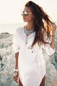 Beautiful boho styled girl wearing white shirt with fashion ethnic jewelery and flash tattoo at the  poster
