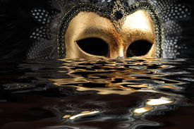 stock photo of masquerade mask  - Venetian mask decorated with gold leaf and embedded with fowl feathers with reflection on water - JPG