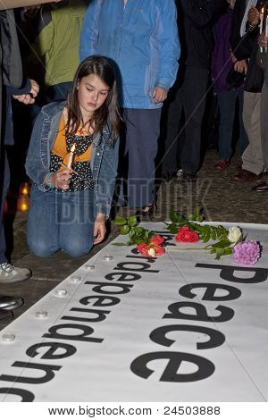 Attendees Of The Peace Walk For Interdependence Light Candles On The Peace Banner In Rememberance Of