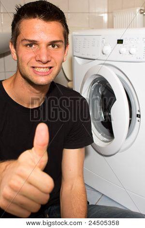 Joven feliz con lavado mashine