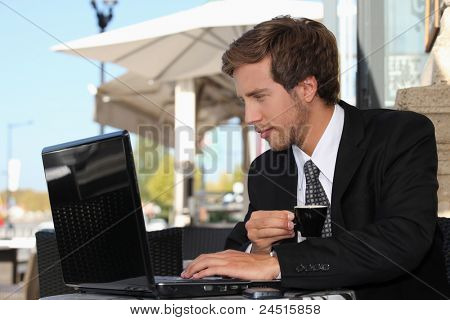 business man drinking coffee and watching his laptop on a street cafe