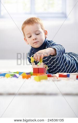 Schöne 3 Jahre alt spielen mit Erstellen von Cubes zu Hause Handauflegen Boden.?