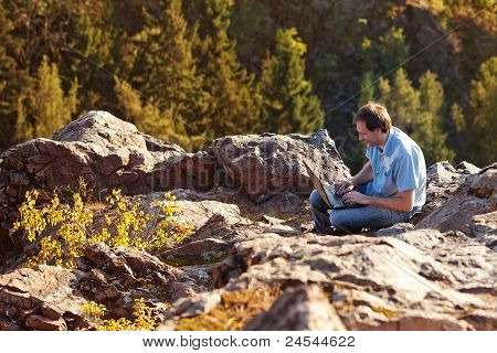 Young Man Using Laptop Sitting On A Rock Slope