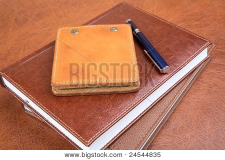 Leather Organizers And  Pen On A Textural Background