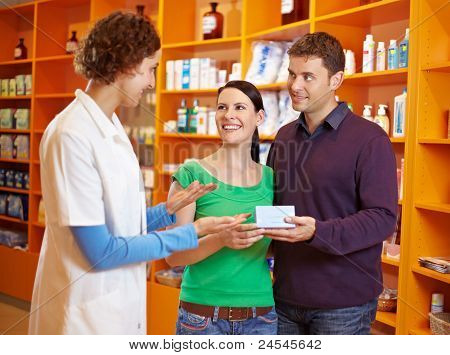 Pharmacist talking to happy couple