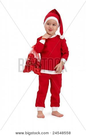Cute kid grimacing in santa costume, sticking tongue, holding red bag.?