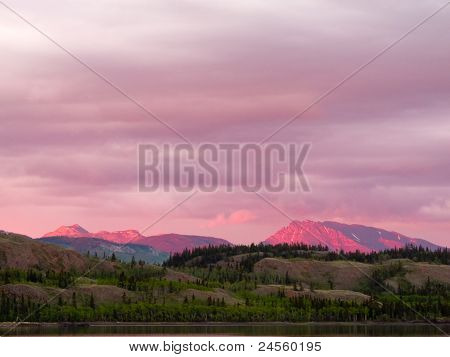 Distant Yukon mountains glowing in sunset light