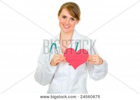 Sonriente médico con corazón de papel