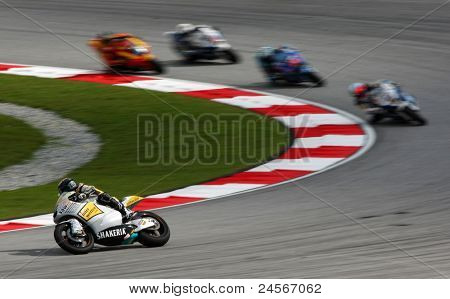 SEPANG, MALAYSIA - OCTOBER 22: Moto2 rider Thomas Luthi (12) races with other riders at the qualifying race of the Shell Advance Malaysian Motorcycle GP 2011 on October 22, 2011 at Sepang, Malaysia.