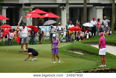 KUALA LUMPUR, MALAYSIA - OCTOBER 16: Aman Blumenherst (black) prepares for her putt on day 4 of the Sime Darby LPGA Malaysia 2011 golf tournament on Oct 16, 2011 in Kuala Lumpur, Malaysia.