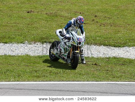 SEPANG, MALAYSIA - OCTOBER 23: Moto2's Anthony West picks his bike up after a fall at turn 15 during warm-up at the Shell Advance Malaysian Motorcycle GP 2011 on October 23, 2011 at Sepang, Malaysia.
