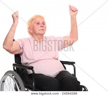 Elderly paraplegic woman sitting in a wheelchair on a white.