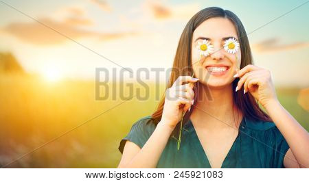 poster of Beauty joyful girl with daysy flowers on her eyes enjoying nature and laughing on summer field. Beau