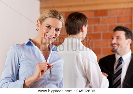 Couple renting apartment from a realtor - a woman is happy about it and stands in the front while in the back the men shaking hands