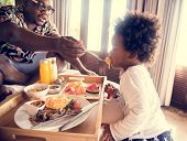 African family having breakfast in bed poster