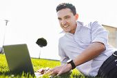Freelance Worker. Experienced Freelance Worker Completing His Tasks Outside While Lying On The Grass poster