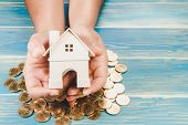 Investor Show Hand Holding A Model Home On A Coin And The Wooden Vintage Background, Saving Money Fo poster