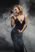 Sexy Young Girl Singer Singing With Silver Retro Microphone On Black Background With Stage Smoke poster