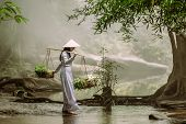 The Vietnamese Girl In The Traditional Dress Is Carrying A Basket With Herbs And Lotuses Crossing A  poster