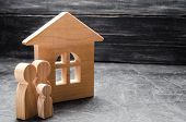 Wooden Figures Of The Family Stand Near A Wooden House. The Concept Of Finding A New Home, Moving. A poster