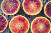 Sliced Blood Oranges Texture. Citrus Background. Cut Ripe Juicy Sicilian Blood Oranges Fruits On Old poster
