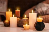 Burning candles on table indoors poster